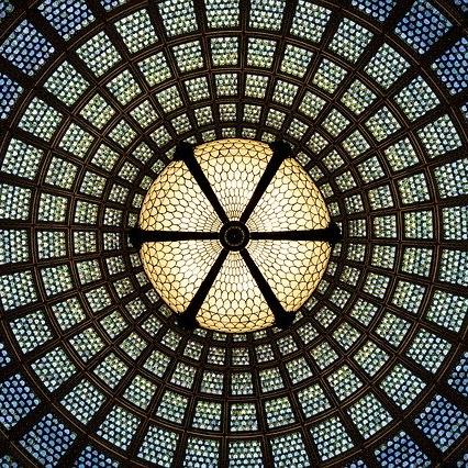 Ein großes rundes, buntes Kirchenfenster, eine runde Struktur mit konzentrischen Kreisen, in der Mitte eine Kreuzform.